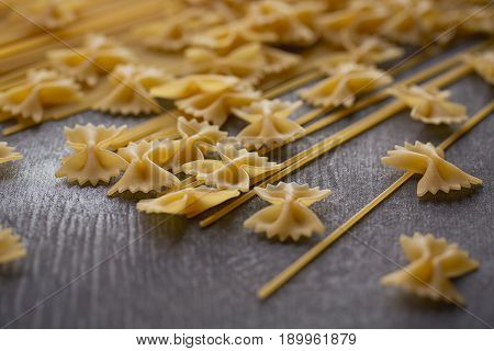 Composition of uncooked italian pasta. Spaghetti farfalle fusilli on dark wooden background. Raw pasta background.