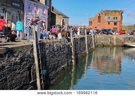Padstow, Cornwall, Uk - April 6Th 2017: People Fishing For Crabs Using Crab Lines On The Harbour Wal