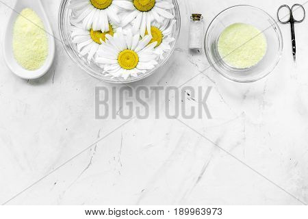 Spa composition on white desk with salt, chamomile, towel and sciccors copyspase top view.