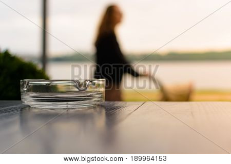 Ashtray on the table. In the background mother with a stroller in a blur on the background of the lake and sunset.