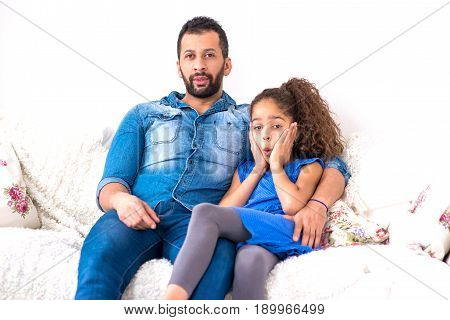 A young black father and his daughter siting together on a couch and looking surprised