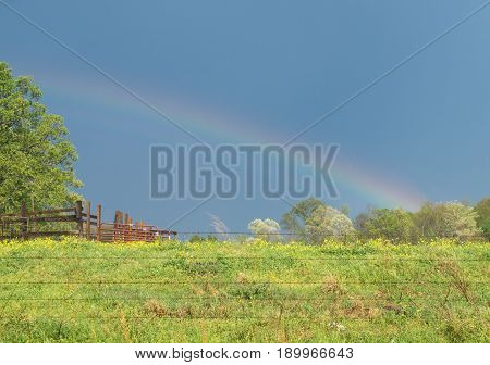 A rainbow appears over green farmland pasture with red fencing. Spring season displays green grass and clear blue sky