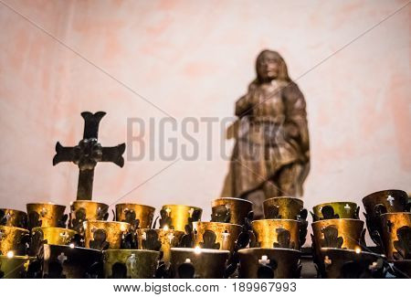 Golden lights illuminate image of cross, prayer candles, and statue. Intentional background blur.