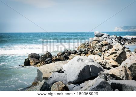 Ocean view with large rocky boulders at shoreline