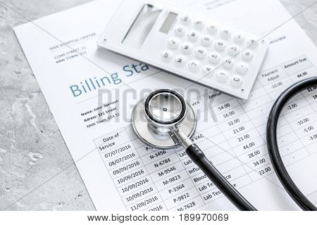medical treatmant billing statement with stethoscope and calculator on stone desk background