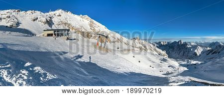 Sunny winter day panoramic view on ski lift at ski-run Alps mountains under snow skiing people ski station cable-way to Zugspitze peak. Ski season in Alps. Famous ski holidays vacatios tours