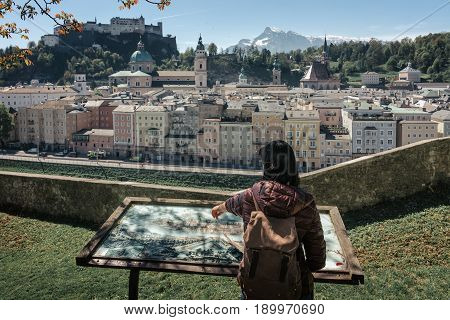 SALBURG, AUSTRIA - 21 APRIL 2016: Austria. Salzburg. The girl tourist on the observation deck at the old maps of the city with views of the Hohensalzburg fortress