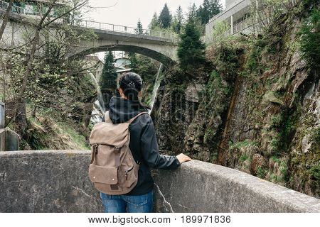 Austria. Bad Gastein - April 22, 2016: Girl traveler with a backpack near the Alpine falls
