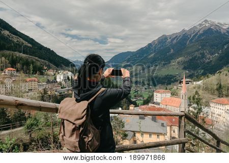 Austria. Bad Gastein - April 22, 2016: The girl traveler with a mobile phone and a backpack is on the observation deck with a view of the Alpine village and mountains