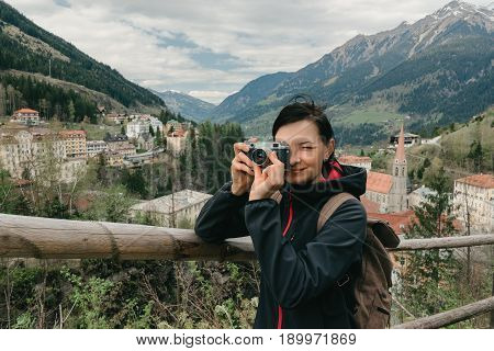Austria. Bad Gastein - April 22, 2016: Girl traveler with a retro camera and a backpack is on the observation deck with a view of the Alpine village and mountains