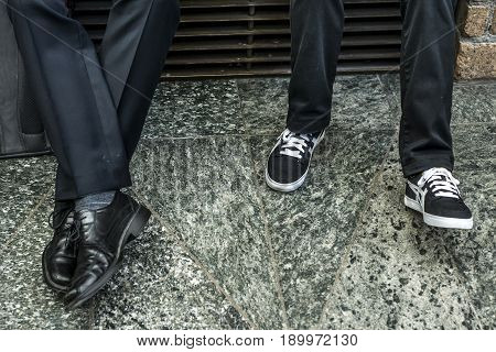 Closeup of two men in suit Variety Leather Shoes and black white sneaker