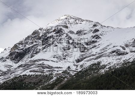 A gorgeous and snow-covered mountain against gray clouds in Banff National Park in Alberta Canada.