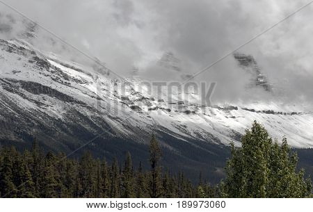 A massive mountain range covered in snow and obscured by clouds in Banff National Park in Alberta Canada.