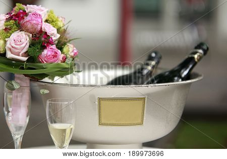 rose flowers and ice cooled sparkling wine and champagne bottle in bucket copyspace text space
