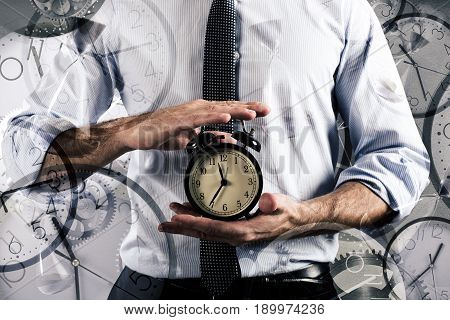 Businessman holds an alarm clock. Concept of delay and time