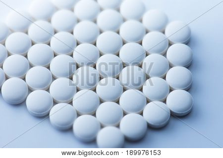 White medicine tablets or  pharmaceutical pills shot from above, in a hexagonal formation. Intentionally shot in surreal bluish tone.