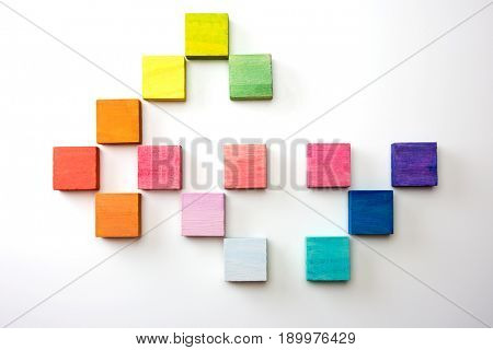 Colored wooden tiles in a arranged pattern, multiple  colors. Arranged on a natural white background, with highlight on upper left corner and natural shadows.