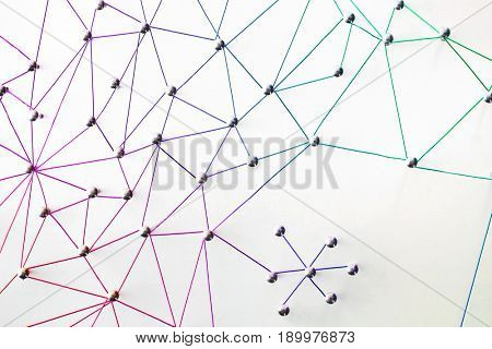 Linking entities. Networking, social media, SNS, internet communication abstract. Small network connected to a larger network. Web of red, pink, purple, blue, green connections on white background.