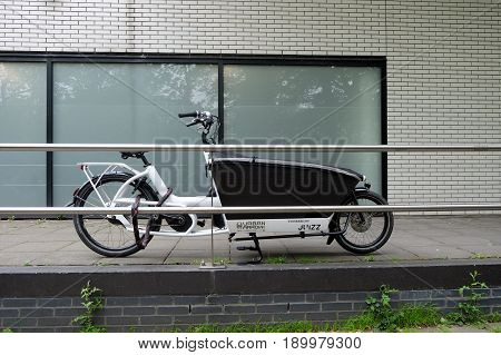 AMSTERDAM NETHERLANDS - MAY 15 2017: Bicycle with a trolley for the children transportation