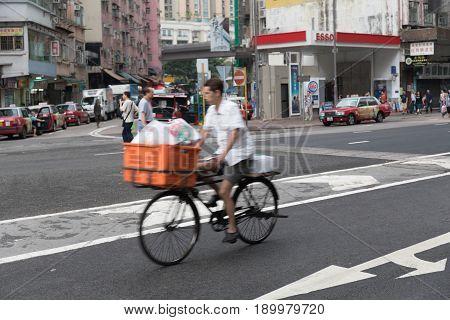 KOWLOON HONG KONG - APRIL 21 2017: Man on Bicycle Driving Fast With Cargo Box in Kowloon Hong Kong.