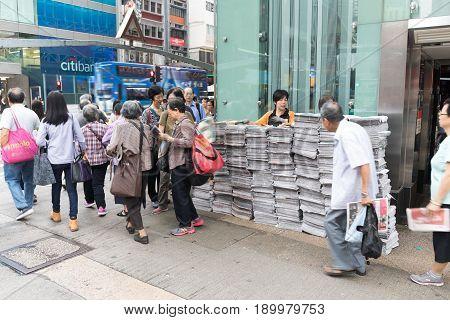 KOWLOON HONG KONG - APRIL 21 2017: People Waiting in Line For Newspapers at Nathan Road Mong Kok in Kowloon Hong Kong.