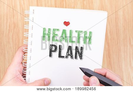 health plan word on notebook with hand holding pencil