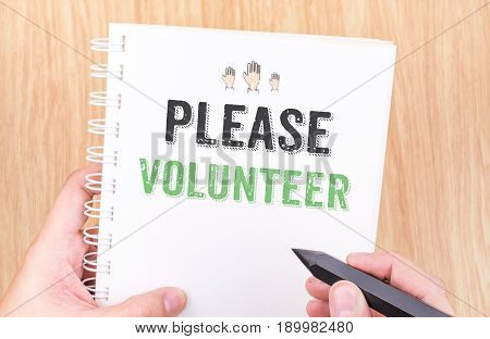 Please Volunteer Word On White Ring Binder Notebook With Hand Holding Pencil On Wood Table,business