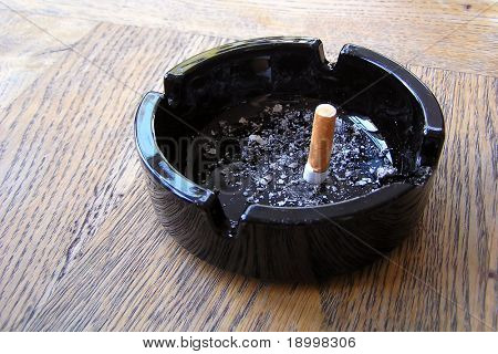 Finished cigarette in black ashtray with some ash.