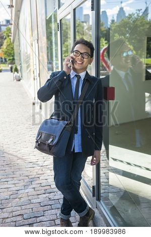 Young asian business man talking on mobile phone outside on city street