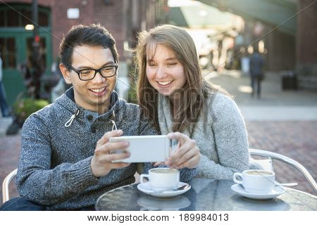 Two young people looking into smartphone on outdoor cafe patio