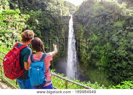 Couple backpacking tourists pointing at Hawaiian waterfall.Tourist girl showing Akaka Falls waterfall on Hawaii, Big Island, USA. Travel tourism young people with backpacks.