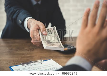 Businessman refusing money Japanese yen bills - anti bribery and corruption concepts