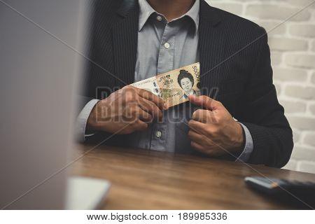 Businessman putting money Korean won banknotes into his suit pocket - corruption concept