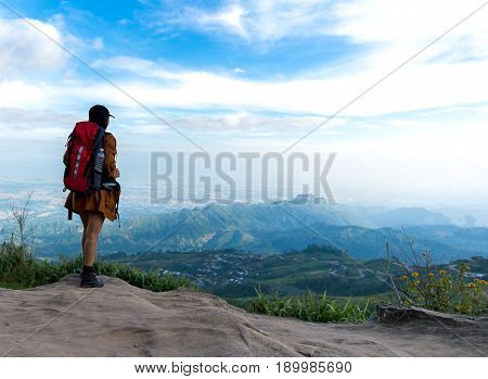Hiker woman look binoculars on the mountain background blue sky Thailand select and soft focus