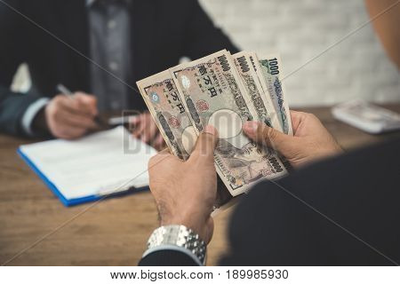 Businessman counting money Japanese yen banknotes while making agreement with partner - loan bribery and corruption concepts