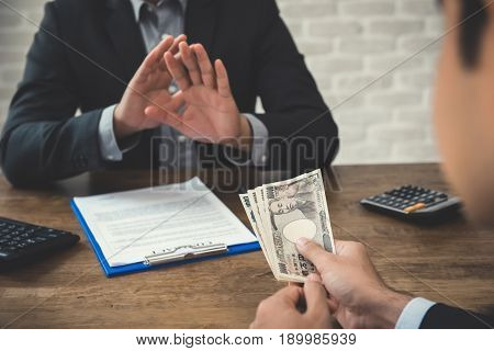 Businessman refusing money being offered by his partner - anti bribery and corruption concepts