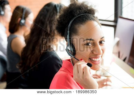 Smiling black businesswoman working in call center as the operator or telemarketer