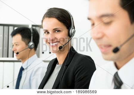 Smiling businesswoman working in call center as a telemarketer or customer service staff