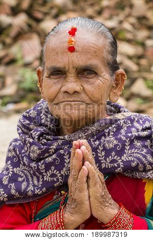 KATHMANDU NEPAL - SEPTEMBER 29 2016 : Portrait old woman in traditional dress with folded hands in street Kathmandu Nepal. Close up
