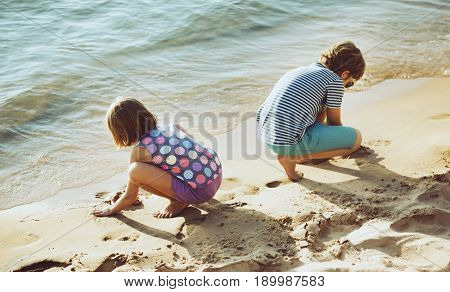 Little children playing sand by the seashore