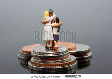 miniature businessman people and family hugs together standing on the coins