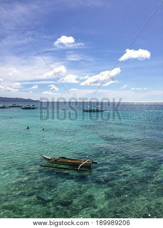 Clear sea with boats and bathers at sunny summer day