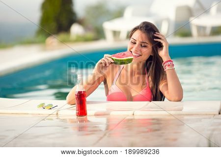 Cute smile brunette young woman refreshing with slice of watermelon and  drink on railing of swimming pool