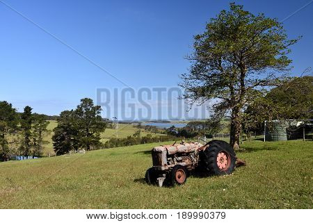 Central Tilba in its idyllic setting near Narooma in New South Wales Australia. Autumn scene in rural New South Wales Australia. Farmland fields and hills.Old tractor on the grass.