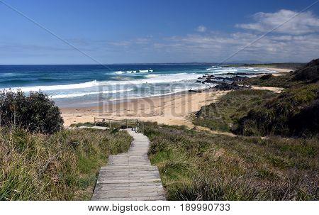 Sea beach wooden walkway path entrance. Sandy ocean beach entrance at 1080 beach.