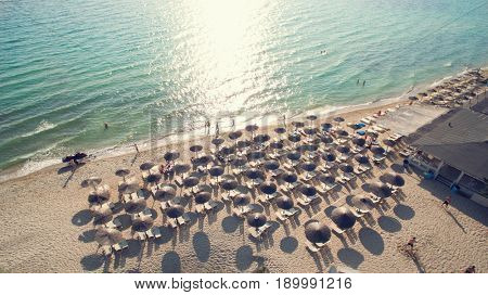 Top view of beach at summer with bathers and parasol