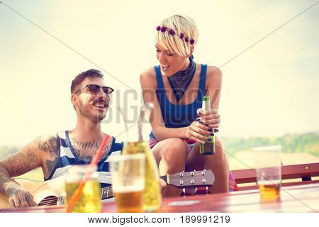 Heavily tattooed guy playing guitar while lassies drinks beer in nature at spring