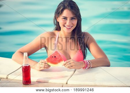 Very charming brunette girl posing on railing of swimming pool with slice of watermelon