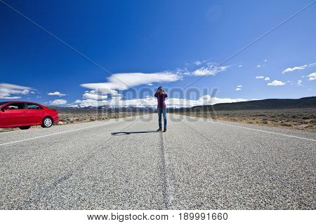 Japanese woman using binoculars on road trip