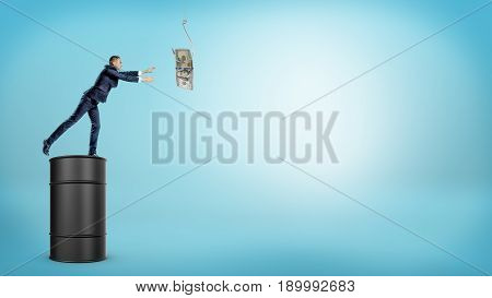A small businessman standing on a large oil barrel and trying to catch a dollar bill from a silver hook. Oil and gas business. Loss of profits. New procurement requirements.